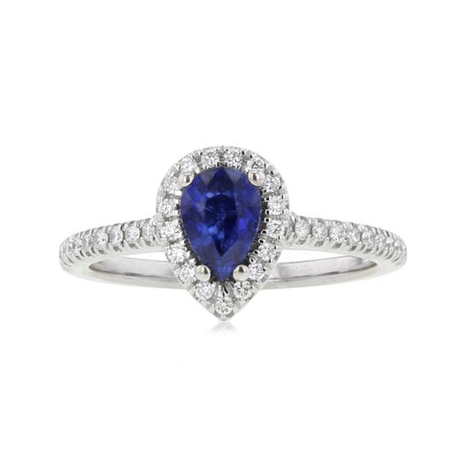 pear-cut blue sapphire center stone set in halo of white diamond rounds that extend onto white gold band