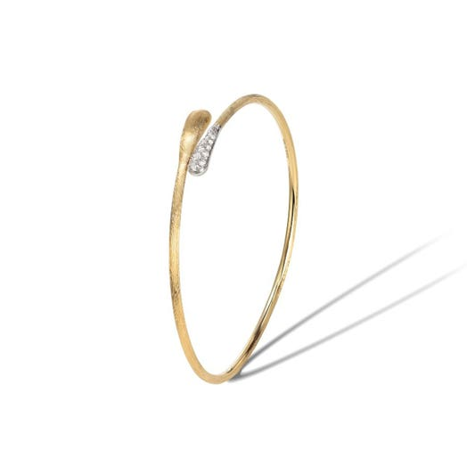yellow gold bracelet cuff with etched design and diamond accents on one end