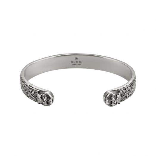 open sterling silver cuff with detailed design and two lions heads at each end
