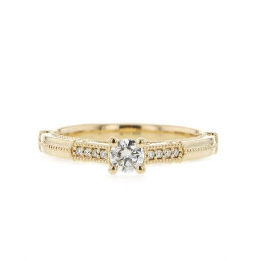 yellow gold ring with milgrain details, four prong set white round center stone with diamond accents on band