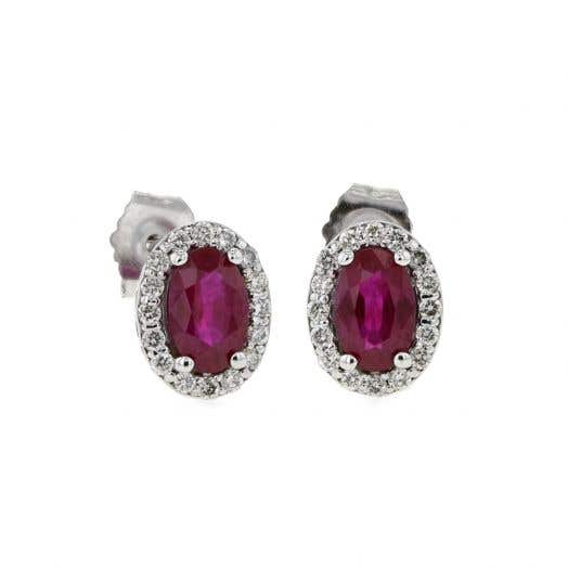white gold stud earrings with oval cut rubies surrounded in halos of white diamonds