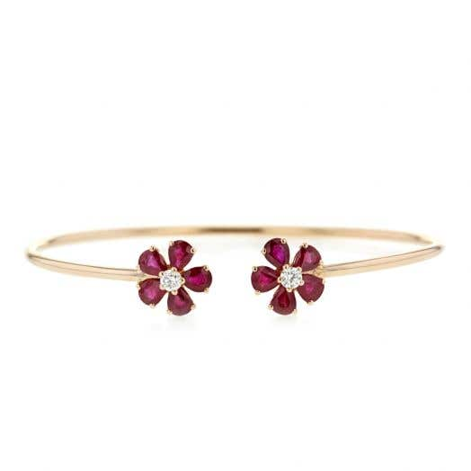 yellow gold open bangle with two flowers on each end with ruby petals and diamond centers