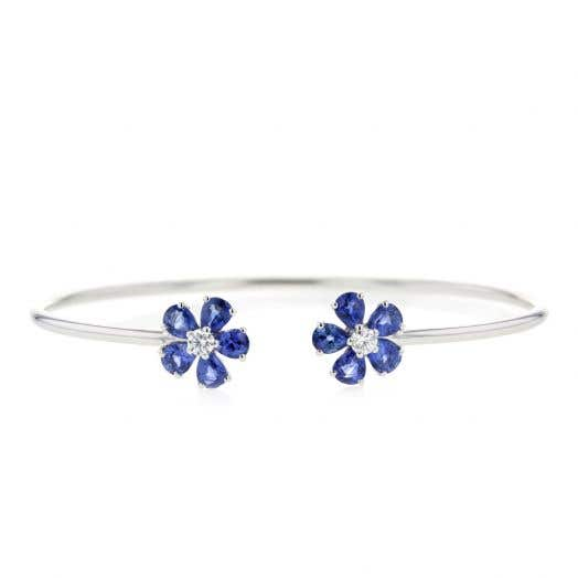 white gold open bangle bracelet with two flowers on each end with sapphie petals and diamond centers