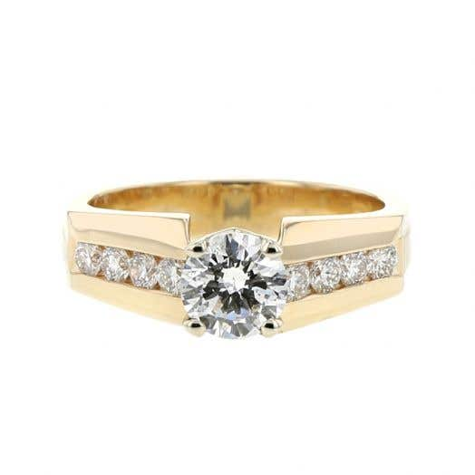 yellow gold band with channel set diamonds on each side of a round-cut diamond center stone